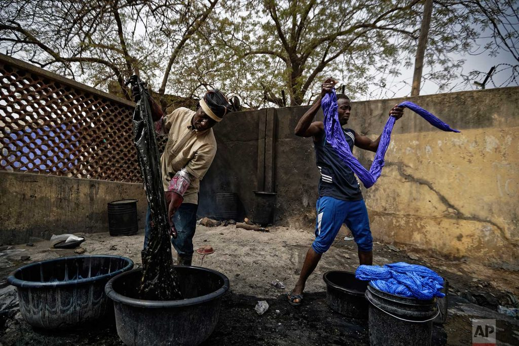 In this photo taken Tuesday, Feb. 19, 2019, craftsmen dye cloths in buckets next to the ancient dye pits of Kofar Mata in Kano, northern Nigeria. (AP Photo/Ben Curtis)