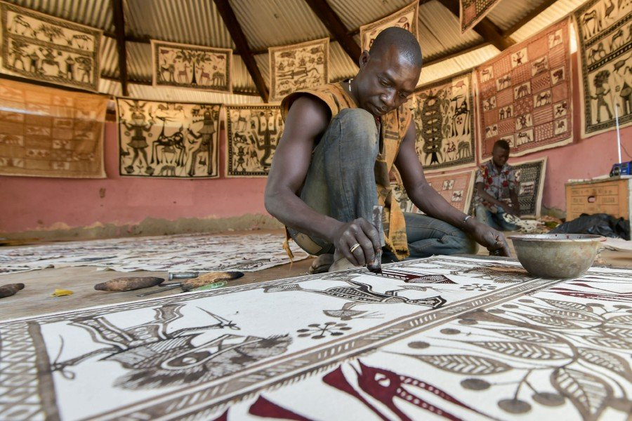 An artist paints on a cotton fabric in his workshop, in the village of Fakaha on January 24, 2019. - Whether in tourist brochures or online, it is not unusual to find references to Picasso's reputed visit to Fakaha, a remote village in northern Ivory Coast, some 650 kilometres (400 miles) from Abidjan, the economic capital. A whole mythology has grown up around the question of Africa and Picasso, who never spoke of having been to Fakaha. (Photo by SIA KAMBOU / AFP)
